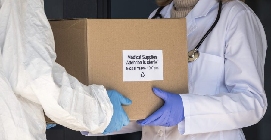 A person in a protective suit is handed a box with protective medical masks to the doctor.